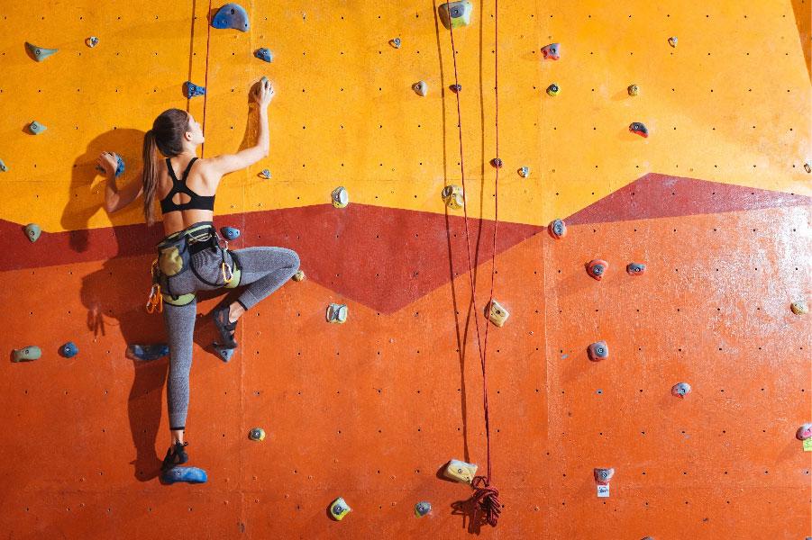 Mujer escalando un muro