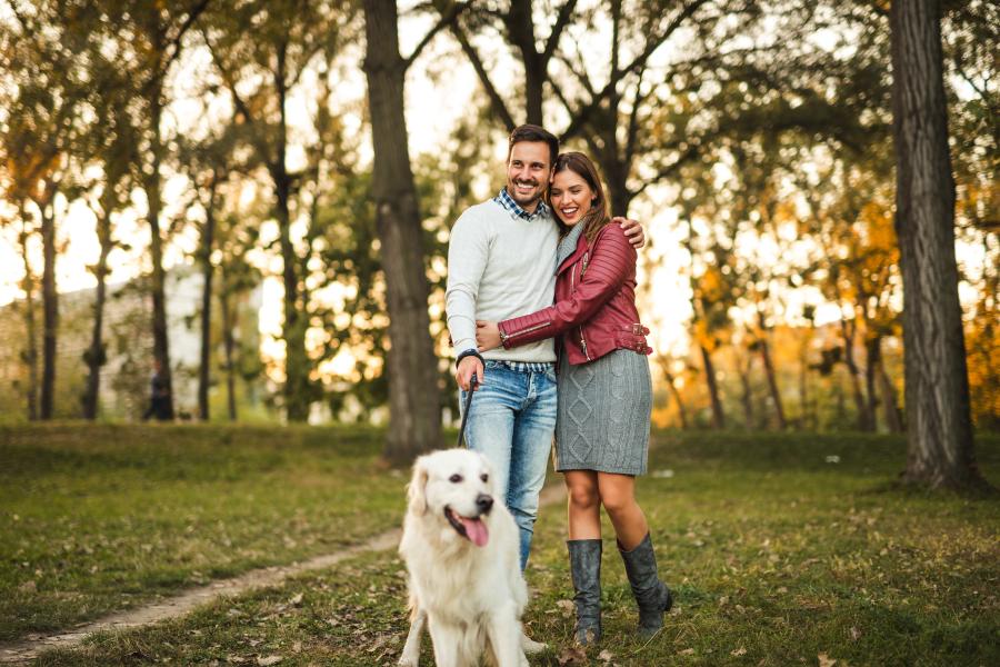 Una pareja paseando con su perro
