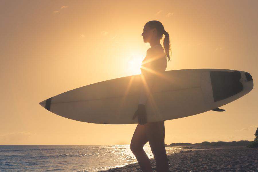 Chica surfeando en Punta del Este al atardecer