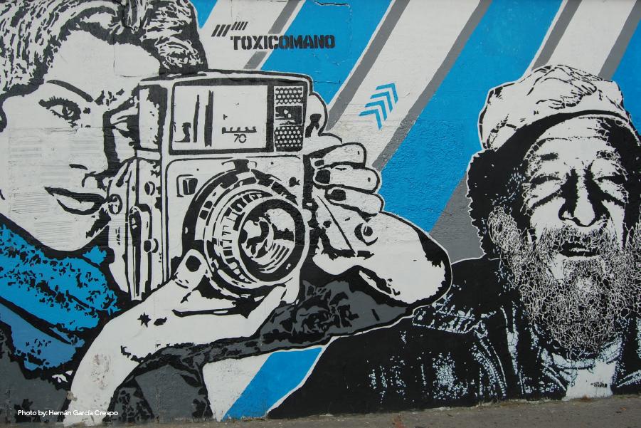 Graffiti de una mujer tomando una foto en tonalidades grises y azul