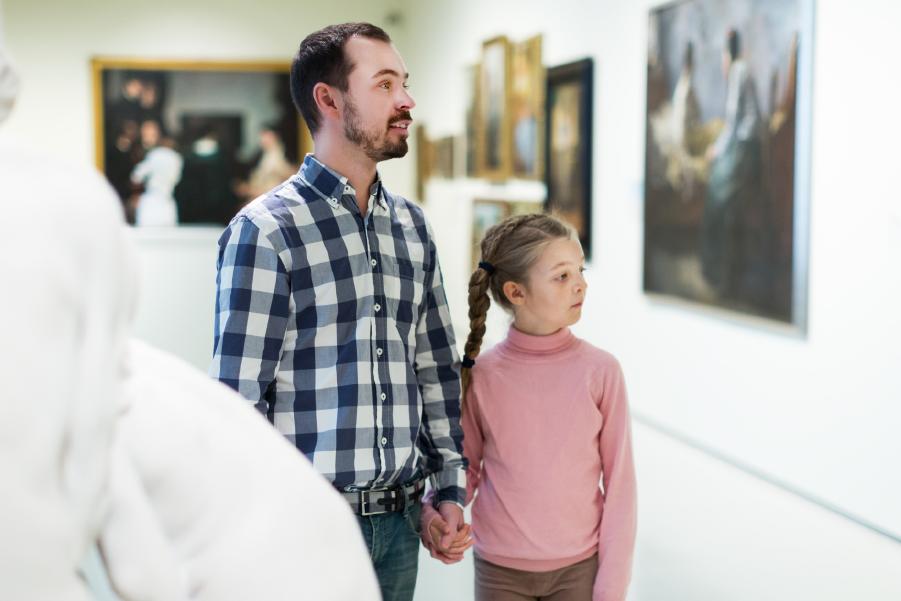Familia observando las obras de arte de un museo