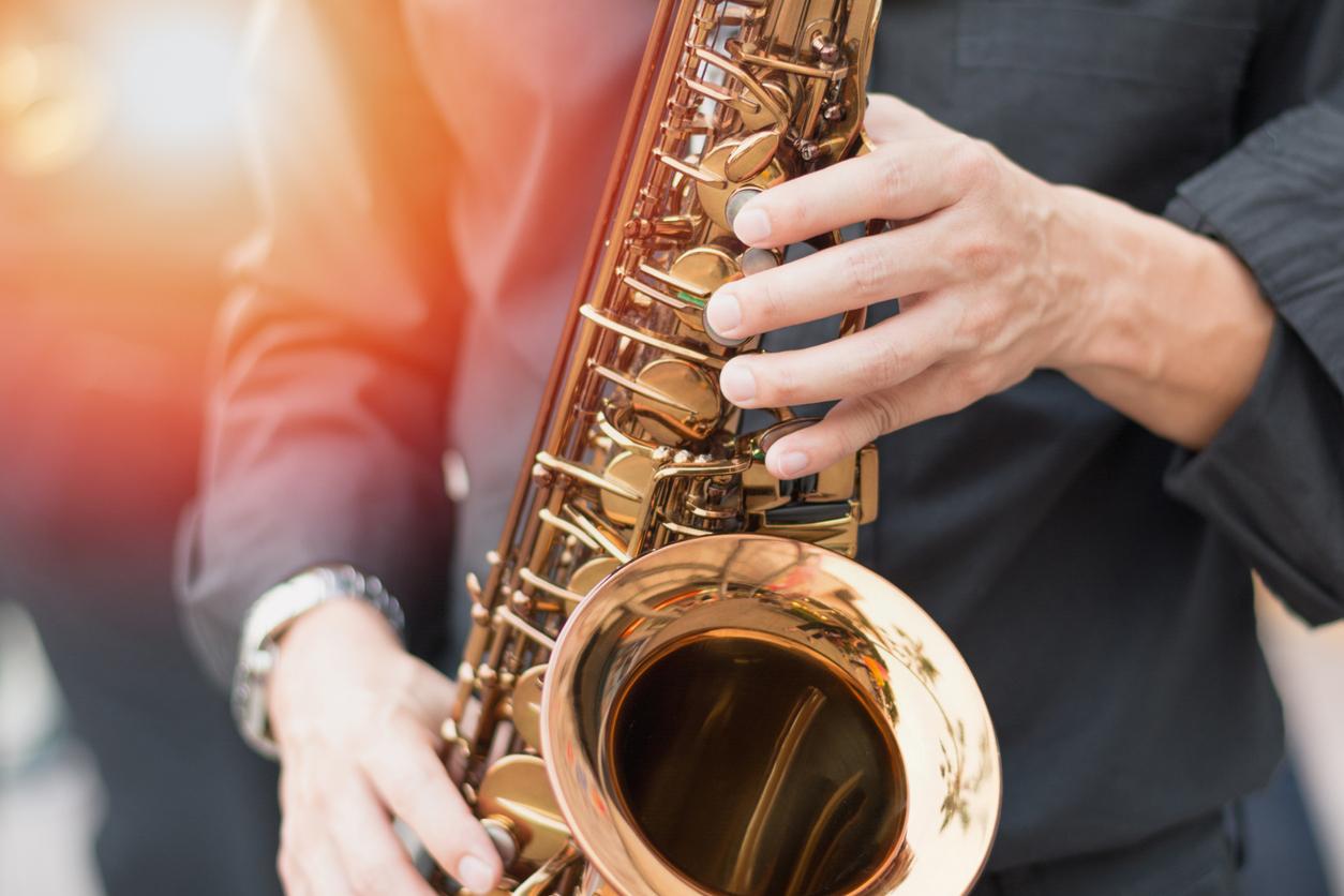 Homem toca jazz com um saxofone.