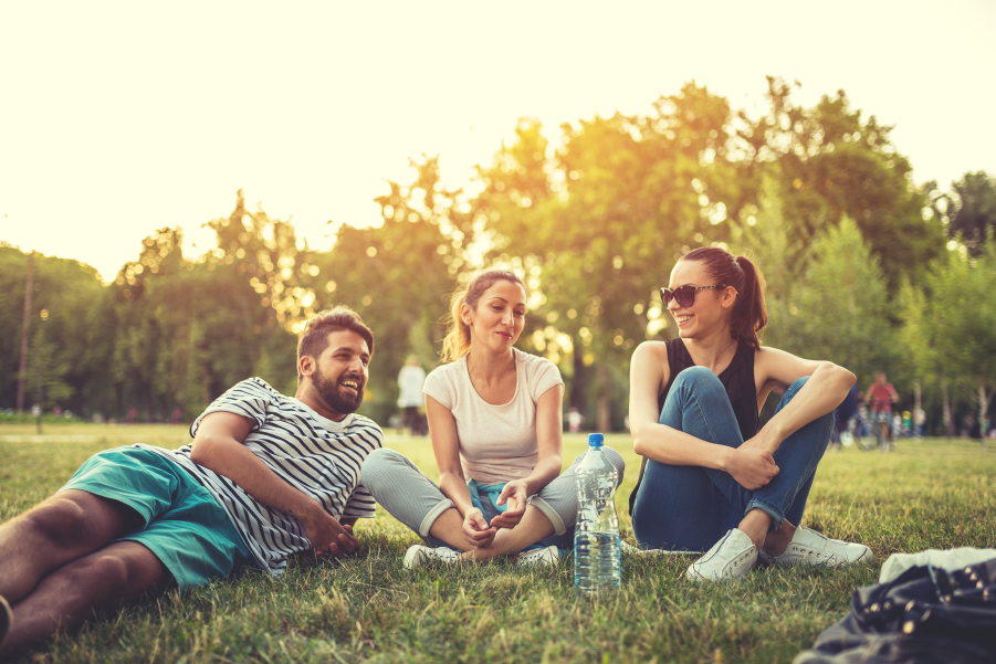 Tres personas sentadas en el cesped de un parque