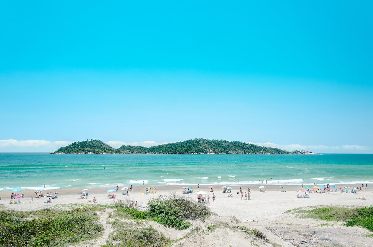 Pessoas na praia do Campeche e a Ilha do Campeche no fundo