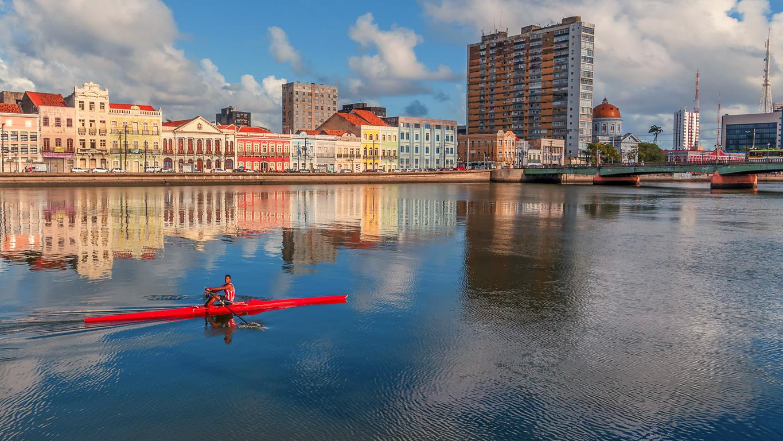 O homem navega ao longo das margens do rio Capibaribe em seu caiaque, em Recife, Brasil.