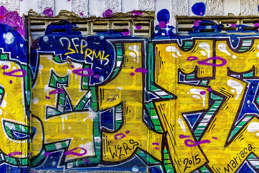 Una pared en la ciudad de Medellín cubierta en colores con algo escrito en letras grandes