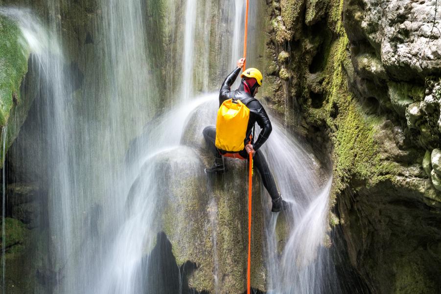Persona escalando en una cascada