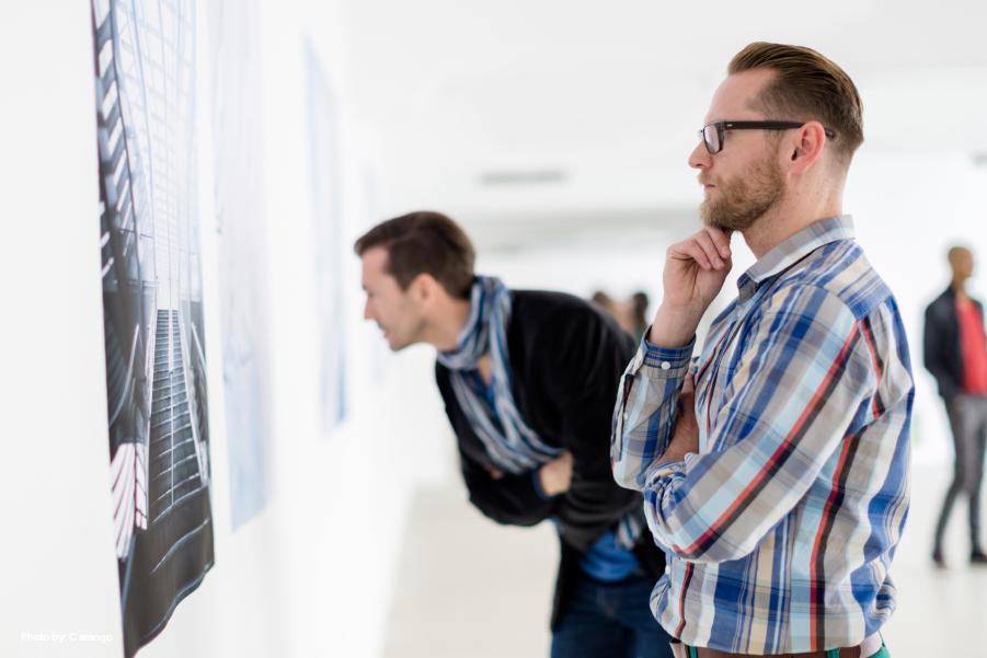 Un par de hombres mirando el arte que se muestra en la pared.