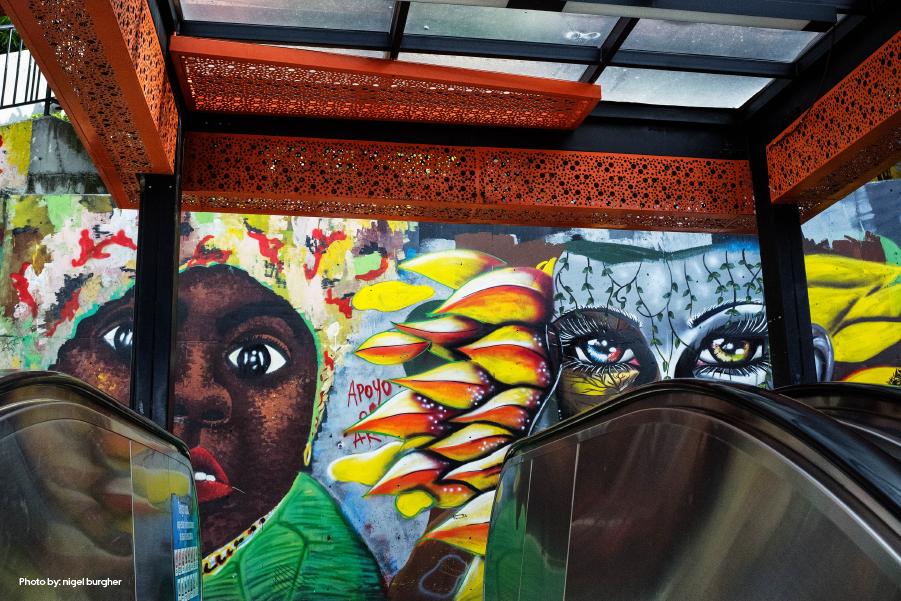 Un mural colorido en Medellín con dos personas pintadas en una pared