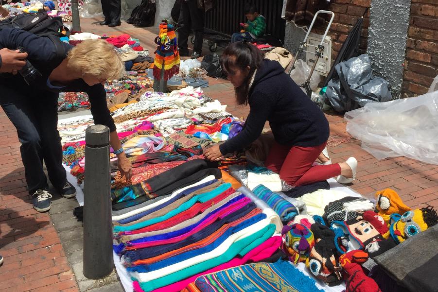 Un cliente pasa por la ropa que se vende en este mercado.