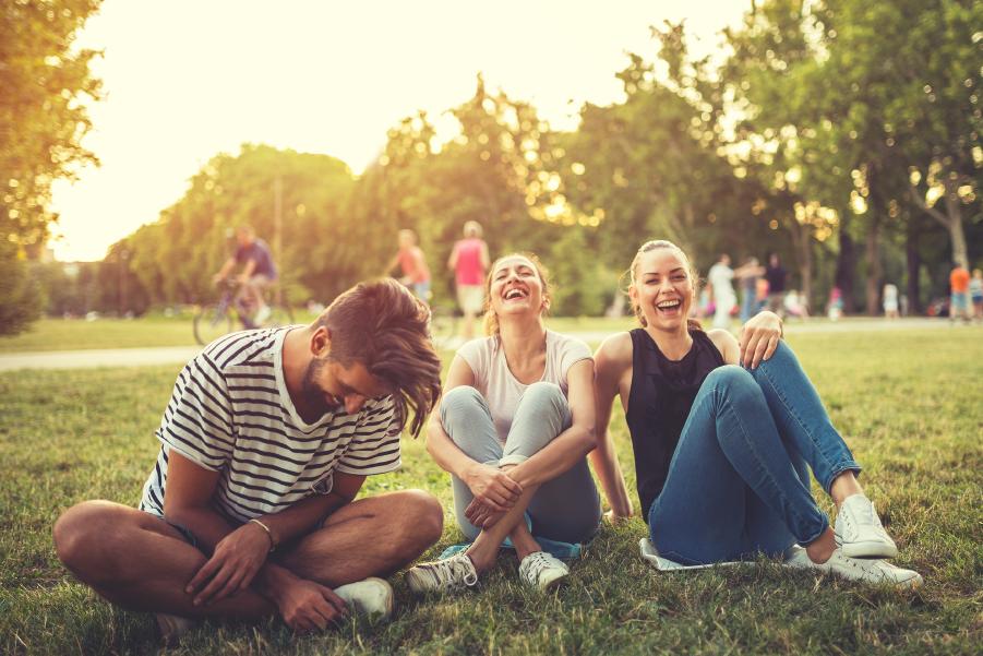 Tres personas riendo sentadas en un parque