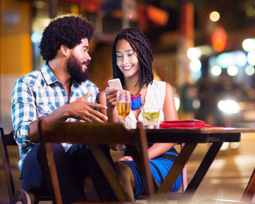 couple looking at their mobile phone in a bar terrace