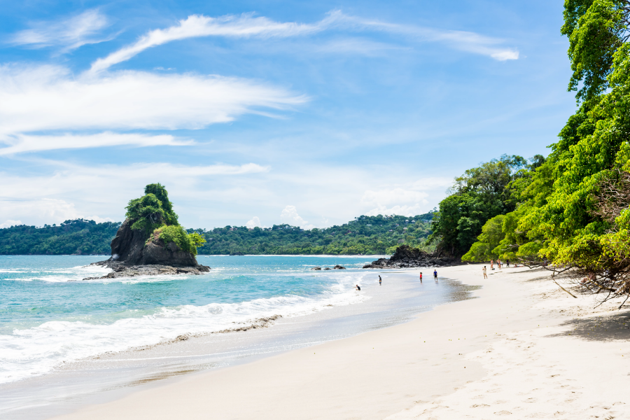 Personas disfrutando de una playa de aguas claras
