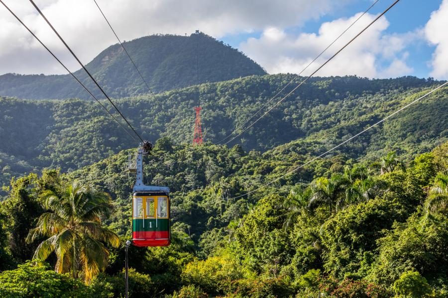 Vista aérea de una cabina del teleférico rodeado de montañas y árboles