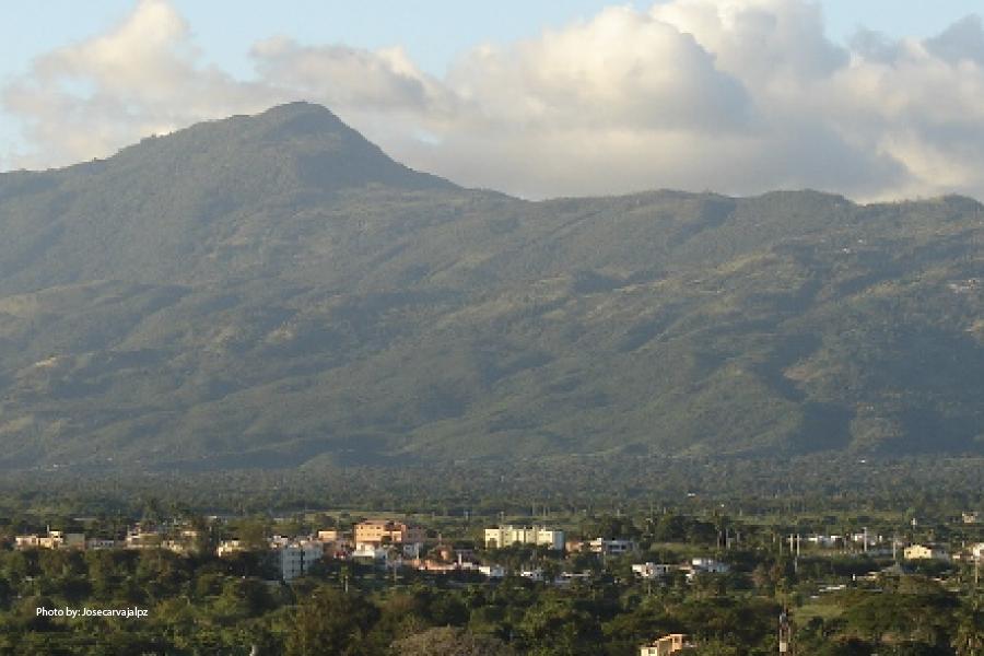 Vista de un paraje montañoso y una llanura repleta de árboles