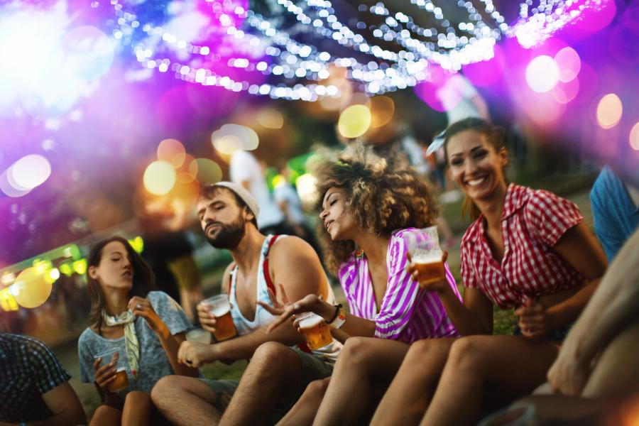 Grupo de amigos sentados en un parque tomando algo mientras escuchan música