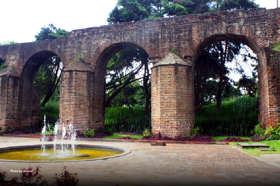 Jardín con una fuente y arcos