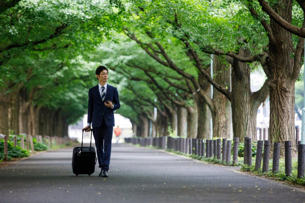 Businessman walks while holding his phone and pulling his rolling luggage.