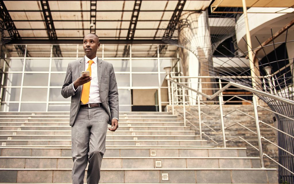 Businessman walks down staircase holding his phone in front of him.