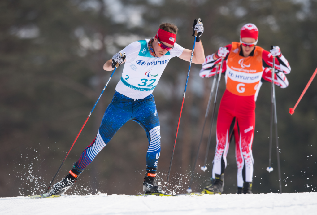 """A front view of Jacob skiing in the Men's 2018 Paralympic 20 kilometer, Visually Impaired, Cross Country Skiing. Jacob is wearing a Team USA spandex race suit, red headband and sunglasses. He's also wearing a race bib with a number """"32"""" on the front. In the background, slightly blurred, are a competing skier and guide racing for Team Canada in red race suits."""