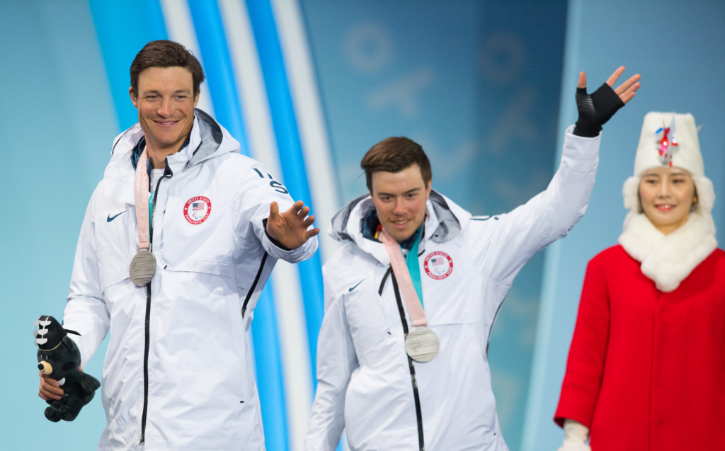"""Jacob (right) and guide Sawyer Kesselheim (left), at the medal ceremony for the Men's 2018 Paralympic 10 kilometer, Visually Impaired, Cross Country Skiing. They are standing side by side, smiling, waving, with silver medals around their necks. They're wearing long, white Team USA jackets, and both holding a stuffed bear, the Pyeongchang Paralympic mascot named """"Bandabi."""" In the background stands one of the ceremonies medal hosts, wearing a red overcoat, white fur scarf and white hat."""
