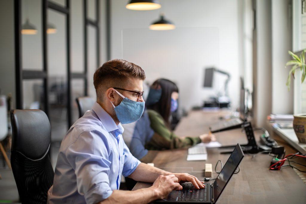 Hombre trabajando de regreso en la oficina usando cubre bocas